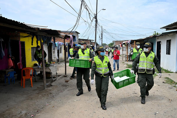 Police officers deliver lunch boxes in Cali, Colombia — a response to reports of hunger during the pandemic.