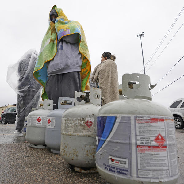 Carlos Mandez waits in line to fill his propane tanks on Wednesday in Houston. Customers had to wait over an hour in the freezing rain to fill their tanks after historic snowfall and widespread power outages in Texas.