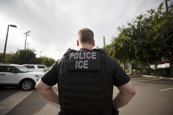 A U.S. Immigration and Customs Enforcement officer looks on during an operation in Escondido, Calif., in 2019. The Biden administration today announced new guidelines that are expected to sharply limit arrests and deportations carried out by ICE.