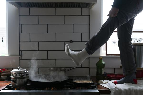 Jorge Sanhueza-Lyon stands on his kitchen counter to warm his feet over his gas stove Tuesday, Feb. 16, 2021, in Austin, Texas.
