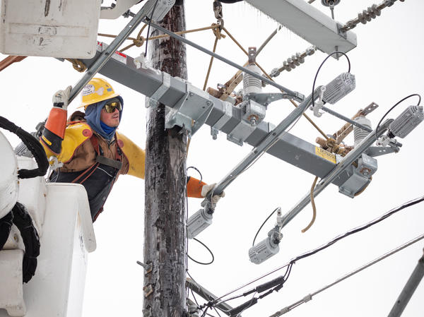 A worker repairs a power line in Austin, Texas, on Thursday. Although power was slowly being restored to much of the state, weather-related water issues persist.
