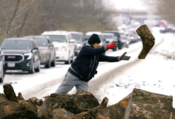 Michelle Terrazas tosses a log of firewood as as people line up to load up Wednesday, Feb. 17, 2021, in Dallas.