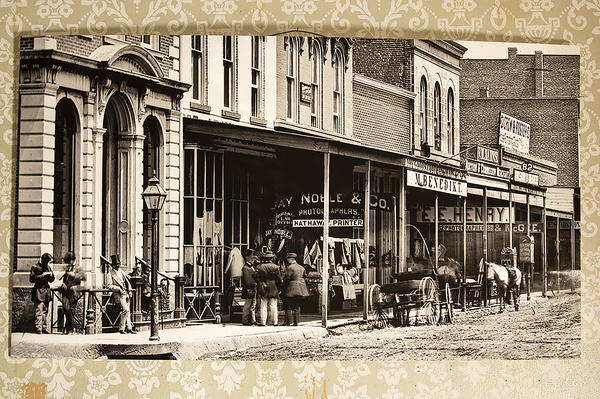 Photographer's studios lined Delaware Street, in the early days of Leavenworth, Kansas. Everyday people rushed to take advantage of the new technology that could produce an image within minutes. This enlargement of a negative from the Everhard collection shows the studios of Jay Noble and E.E. Henry.