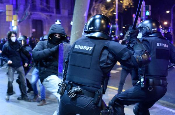 Protesters clash with Mossos d'Esquadra, the Catalan police force, following a demonstration Saturday in Barcelona against the imprisonment of Spanish rapper Pablo Hasel.