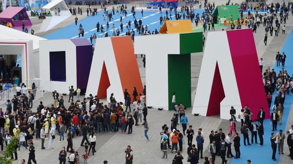 "Visitors walk past the giant word ""Data"" during the Guiyang International Big Data Expo 2016 in southwestern China. China says it's determined to be a leader in using artificial intelligence to sort through big data. U.S. officials say the Chinese efforts include the collection of hundreds of millions of records on U.S. citizens. The photo was released by China's Xinhua News Agency."