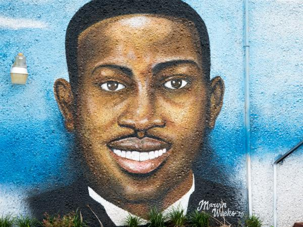 """A mural depicting Ahmaud Arbery in July 2020 in Brunswick, Ga. Gregory McMichael, Travis McMichael, and William """"Roddie"""" Bryan are facing murder charges in connection with his death."""