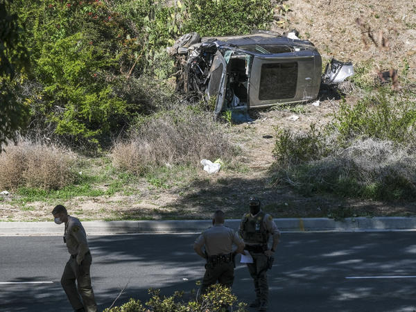 A vehicle rests on its side after a rollover accident involving golfer Tiger Woods along a road in the Rancho Palos Verdes section of Los Angeles on Tuesday. Woods suffered leg injuries in the one-car accident and was undergoing surgery, authorities and his agent said.
