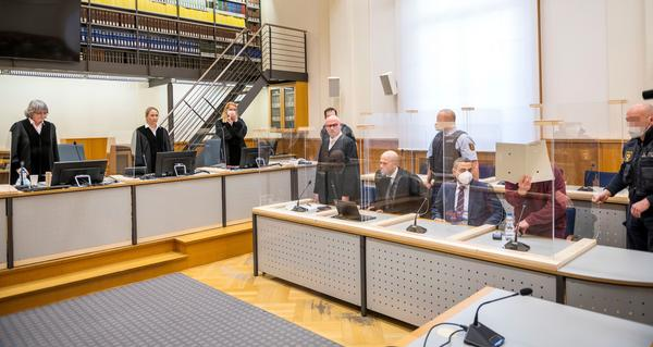 Presiding judge Anne Kerber (left) stands before handing the verdict to Syrian defendant Eyad al-Gharib (right, face hidden under a folder) Wednesday in Koblenz. Gharib, 44, a former Syrian intelligence service agent, was sentenced to 4 1/2 years in jail for complicity in crimes against humanity in the first court case over state-sponsored torture by the Syrian government.