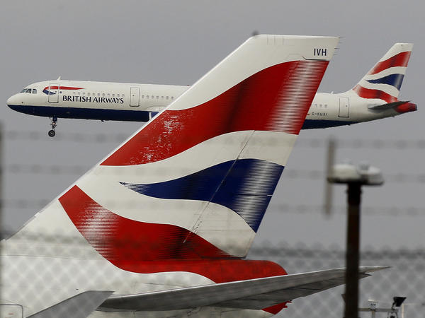 A British Airways plane comes in to land behind a tail fin at Heathrow Airport in London. On Friday, the head of the group that owns BA called for instituting an electronic health pass for passengers as the company announced steep losses due to COVID-19.