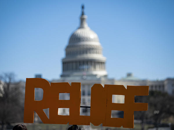 The U.S. Capitol is seen behind a sign during a demonstration in support of COVID-19 relief, organized by Shutdown DC, on the National Mall.