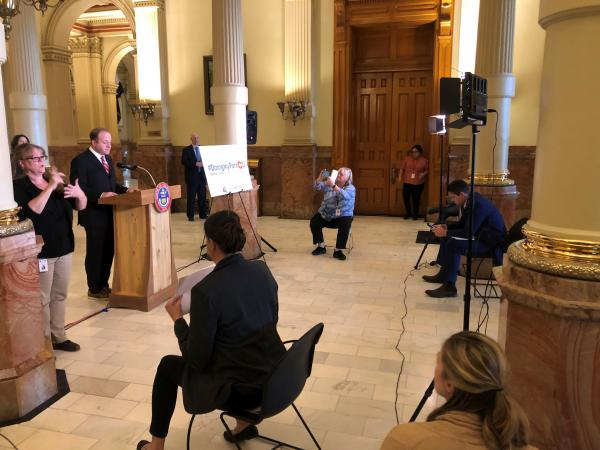 Gov. Jared Polis speaks at the state Capitol about his order to close dine-in sections of bars and restaurants in the state. Reporters were required to sit far apart as the COVID-19 pandemic escalates in the U.S.