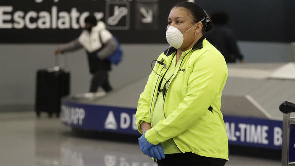 Customer service agent April Brown wears a protective mask and gloves as she helps people at the baggage claim at Hartsfield-Jackson Atlanta International Airport last month.