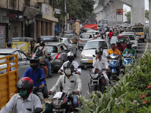 People wearing face masks ride past a busy street on Friday in Hyderabad, India. India crossed 1 million coronavirus cases on Friday, third only to the United States and Brazil.