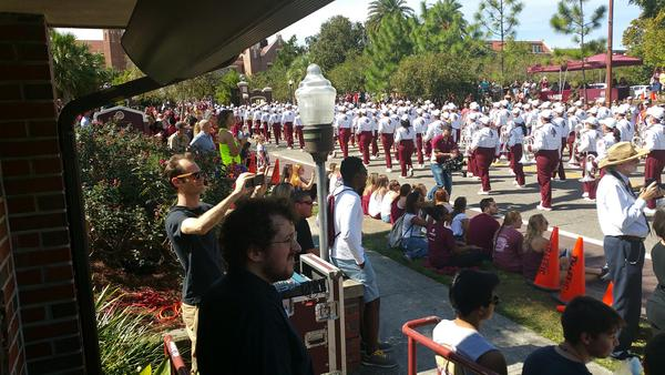 The FSU Marching Chiefs march down the street as a crowd watches, cheers and takes photos during the 2016 Homecoming Parade.