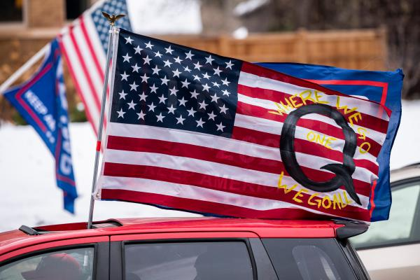 A car with a flag endorsing the QAnon conspiracy theory drives by as supporters of President Trump gather for a rally outside the Governor's Residence in St. Paul, Minn., on Nov. 14.