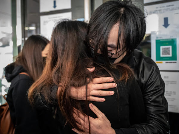 Mike Lam King-nam, who participated in the 2020 pro-democracy primary elections, gives a hug to his wife ahead of reporting to police on Sunday in Hong Kong.