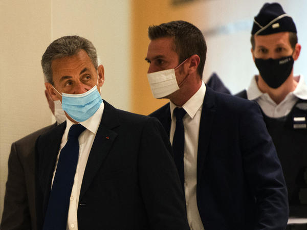 French former President Nicolas Sarkozy (left) arrives to hear the verdict in a corruption trial at Porte de Clichy court house in Paris on Monday.