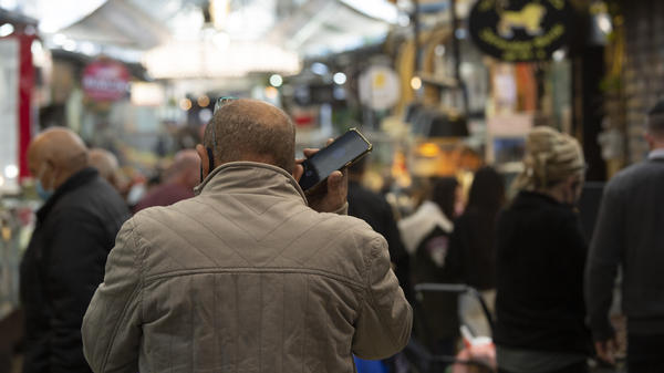 A man speaks on his mobile phone in the Mahane Yehuda market in Jerusalem in December. In the early days of the pandemic, Israel began using a mass surveillance tool on its own people, tracking civilians' mobile phones to halt the spread of the coronavirus.