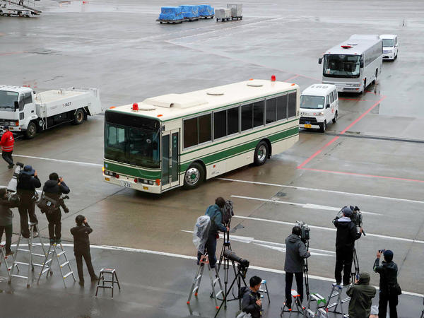 A bus believed to be carrying former U.S. special forces member Michael Taylor and his son Peter, who allegedly staged the operation to help fly former Nissan chief Carlos Ghosn out of Japan in 2019, leaves Narita International Airport in Japan on Tuesday.