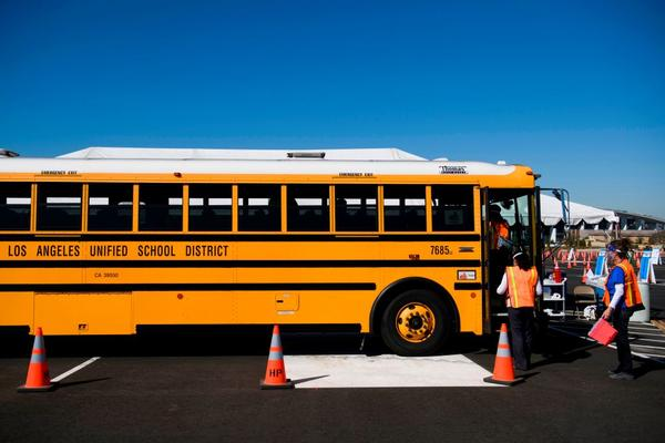 Vaccination site workers board a school bus transporting education workers as it arrives at a mass vaccination site on March 1, 2021 in Inglewood, California. The vaccination site is part of a plan from the Los Angeles Unified School District (LAUSD) and State of California to reopen all district elementary schools by mid-April. (Patrick T. Fallon/AFP/Getty Images)