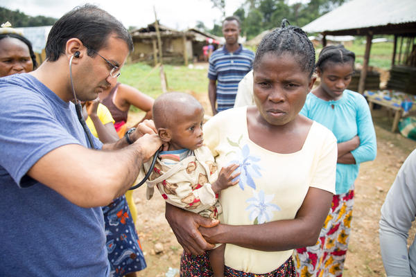 """Dr. Raj Panjabi, the newly named head of the President's Malaria Initiative, treating patients during a visit to Liberia, where he was born and lived until 1990. He'll lead the effort to prevent and treat malaria around the world. Each year, some 400,000 people die of a disease that, he notes, is """"preventable and treatable."""""""