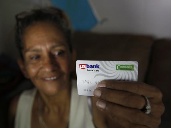 Stockton, Calif., resident Susie Garza displays the debit card on which she received a monthly stipend as part of a pilot universal basic income program. The program began in 2019, when this photo was taken.