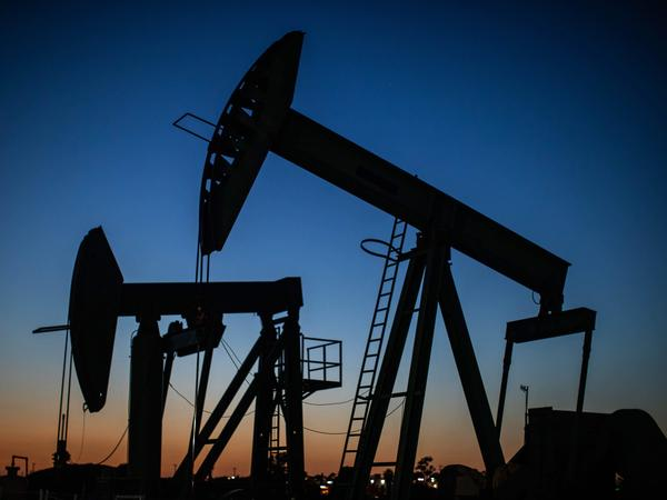 Oil pump jacks operate at dusk in Long Beach, Calif., on April 21, 2020. After getting burned by the oil industry's previous boom-and-bust cycles, Wall Street now wants energy companies to pump less crude, not more.