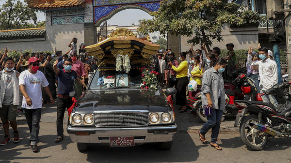 Bystanders flash a three-fingered sign of resistance as the body of Kyal Sin leaves the Yunnan Chinese temple in Mandalay, Myanmar earlier this week.