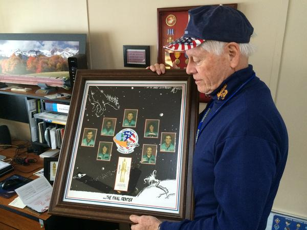 Allan McDonald in 2016 with a commemorative poster honoring the seven astronauts killed aboard the space shuttle Challenger, and McDonald's attempt to postpone the launch.
