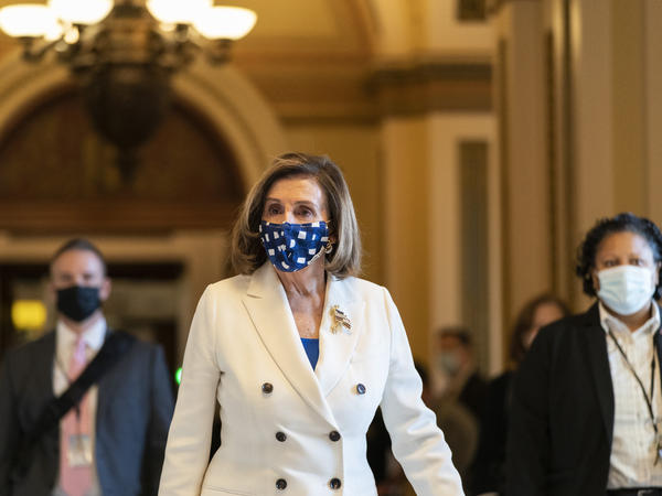 """House Speaker Nancy Pelosi walks from the House floor during the vote on the $1.9 trillion COVID-19 relief bill Wednesday. Despite Republican criticism that the bill has provisions unrelated to the pandemic, Pelosi insists the bill is """"coronavirus-centric."""""""