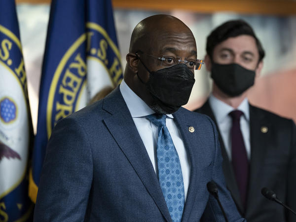 Sen. Raphael Warnock, D-Ga., left, accompanied by Sen. Jon Ossoff, D-Ga., speaks during a news conference, before the vote on the Democrat's $1.9 trillion COVID-19 relief bill on March 10, 2021.