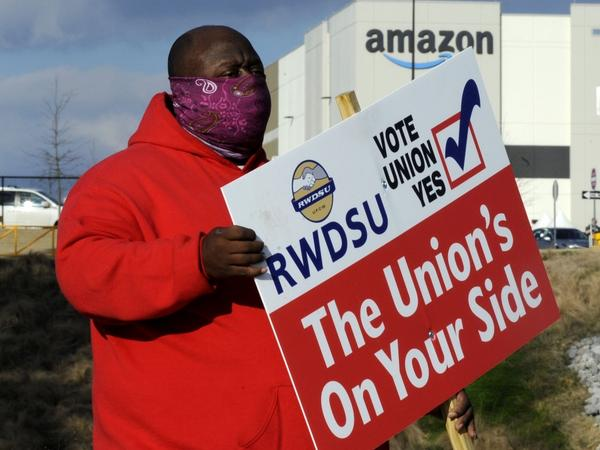Michael Foster of the Retail, Wholesale and Department Store Union holds a sign outside an Amazon warehouse in Bessemer, Ala., where workers are voting on whether to unionize.