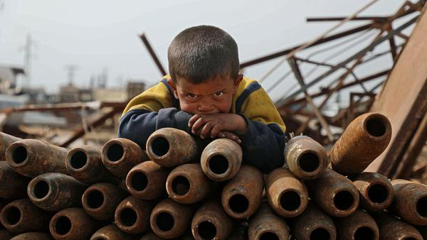 A Syrian child poses atop a stack of neutralized shells at a metal scrapyard on the outskirts of Maaret Misrin town in the northwestern Idlib province, Syria last week.