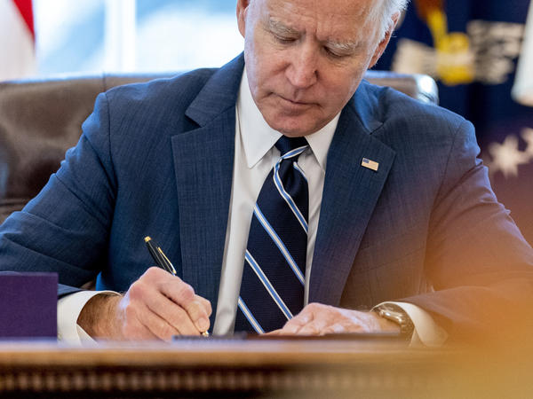 President Biden signs the American Rescue Plan in the Oval Office of the White House on Thursday. Included in the plan is a monthly allowance for many American families that could be a potential financial-life-changer.