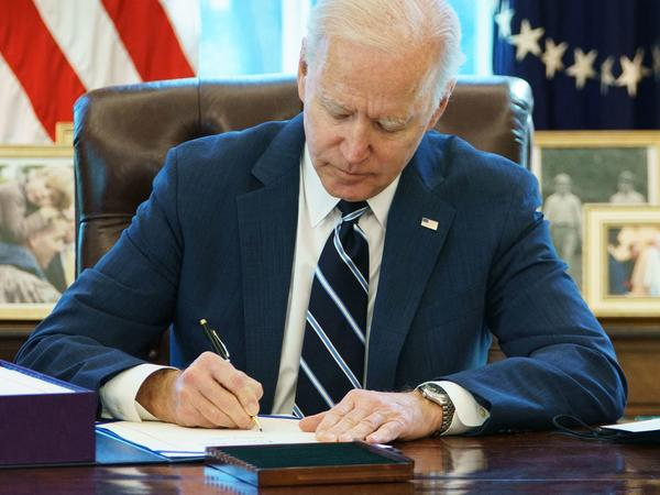President Biden signs the American Rescue Plan Thursday in the Oval Office. The $1.9 trillion economic stimulus bill includes $1,400 stimulus checks for most Americans.