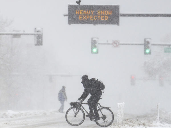 People cross the road as a sign warns of heavy snow on Sunday in Denver. A winter storm closed roads, affected flights and knocked out power in Arizona, Wyoming, Nebraska and Colorado through the weekend.