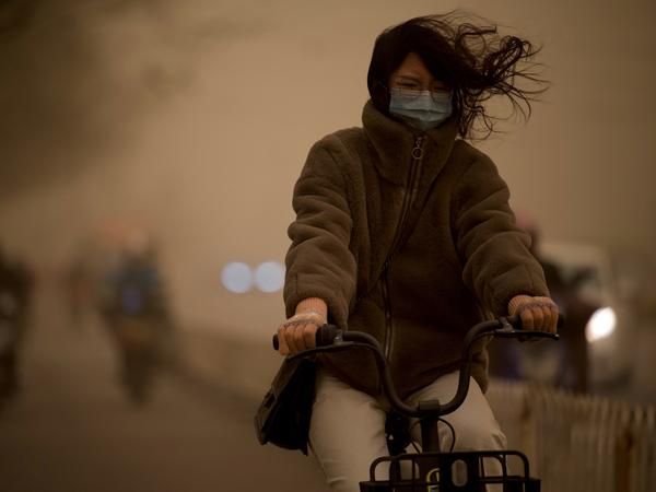 A woman cycles along a street during a sandstorm in Beijing on Monday.