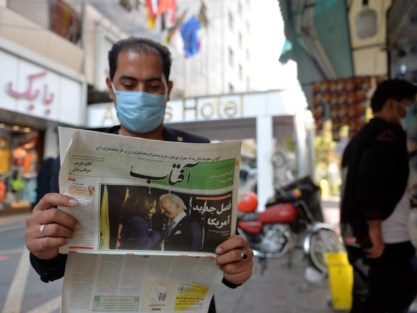 A man reads the news about the U.S. elections on Nov. 9 in Tehran. Many Iranians are hopeful that President Biden will lifts sanctions imposed on Iran by his predecessor.