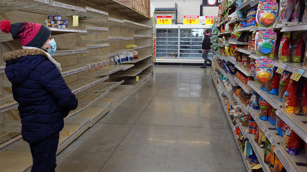 A shopper walks past a mostly bare shelf as people stock up on necessities at the H-E-B grocery store in Austin, Texas, on Feb. 18. A devastating winter storm that hit the middle of the country last month helped send retail sales tumbling.