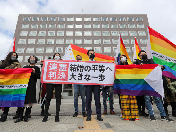 "Supporters celebrate the district court's ruling on Japan's same-sex marriage ban with a flag reading ""unconstitutional decision"" in Sapporo, Hokkaido prefecture, on Wednesday."