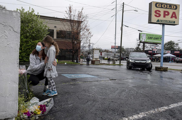 Mallory Rahman and her daughter Zara Rahman, 4, bring flowers to the Gold Spa in Atlanta on Wednesday, the day after eight people were killed at three massage spas in the Atlanta area. Authorities have arrested Robert Aaron Long, 21, in the shootings in Atlanta and Cherokee County, Ga.