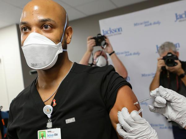 Dr. Hansel Tookes made sure his first dose of Pfizer's COVID-19 vaccine at Jackson Memorial Hospital in Miami on Dec. 15. was televised, as a way to combat hesitancy.