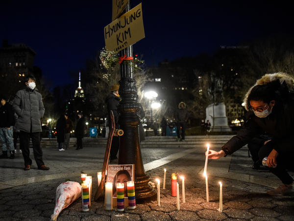 A mourner lights candles for the victims of Tuesday's shootings in Atlanta at a vigil in New York City, one of many across the country this week.