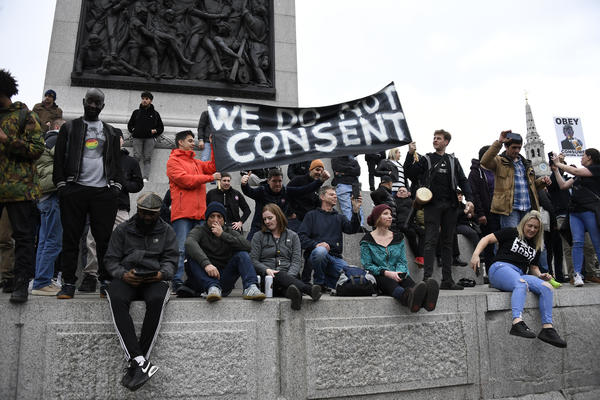 People without face masks attend a protest against government restrictions to curb the spread of the coronavirus in London on Saturday.