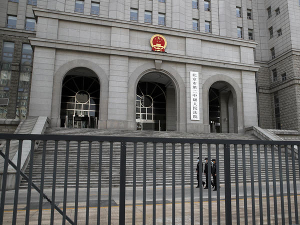 Policemen wearing face masks patrol at the compound of No. 2 Intermediate People's Court in Beijing on Monday, as Canadian Michael Kovrig went on trial in a closed courtroom for espionage.