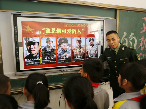 A paramilitary police officer talks next to a screen showing frontier soldiers of the People's Liberation Army during an event at a primary school in Wuzhishan, Hainan province, China, on Feb. 22. On the screen are (L-R) Qi Fabao, who was seriously wounded in the border clash with Indian troops in June last year, and four who were killed: Chen Hongjun, Chen Xiangrong, Xiao Siyuan and Wang Zhuoran.