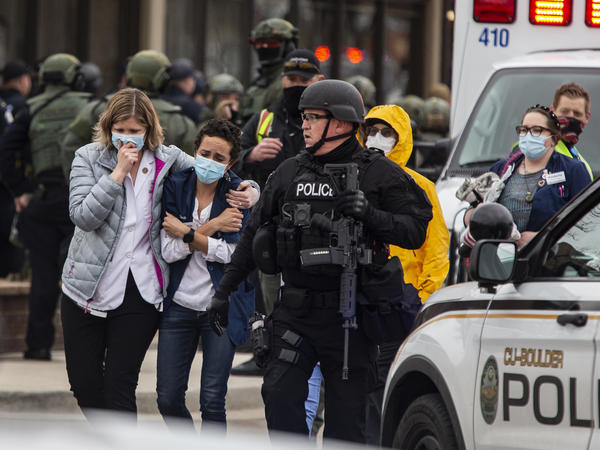 Health care workers walk out of a King Soopers grocery store after a gunman opened fire Monday in Boulder, Colo.