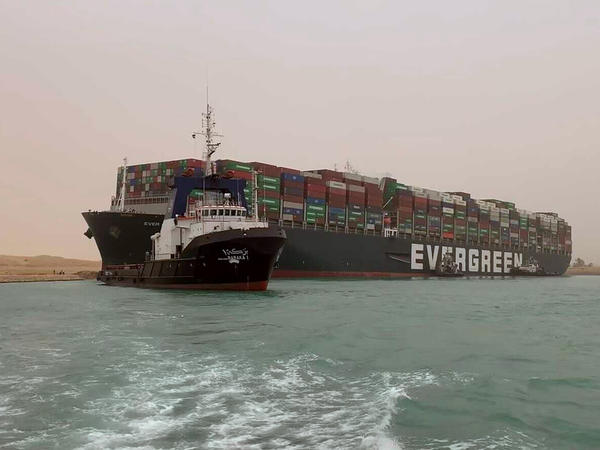 A boat navigates in front of a massive cargo ship that sits grounded after it turned sideways in Egypt's Suez Canal, blocking traffic in a crucial East-West waterway for global shipping. An Egyptian official warned Wednesday it could take at least two days to clear the ship.