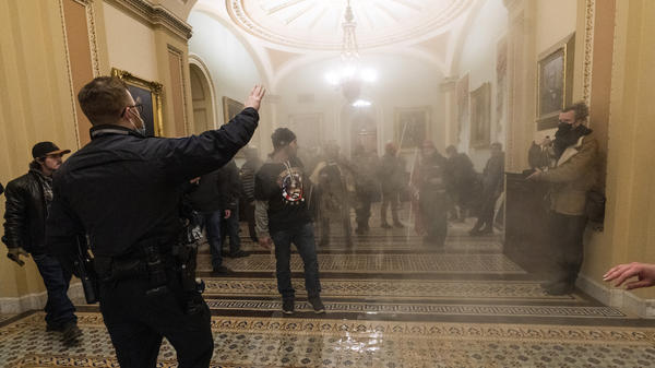 Smoke fills the walkway outside the Senate chamber as U.S. Capitol Police confront rioters inside the Capitol on Jan. 6.