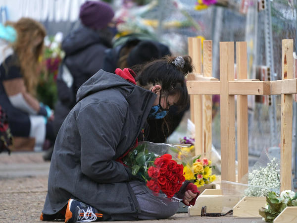 Star Samkus, who works at a King Soopers grocery store in Boulder, Colo., and knew three of the victims of a mass shooting there a day earlier, kneels in front of crosses put up for the victims outside the store on Tuesday.